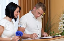 Le marié et la jeune mariée dans le bureau d'enregistrement se marient  image libre de droits