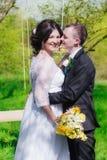 Le marié et la jeune mariée dans une robe blanche font du jardinage au printemps Photographie stock