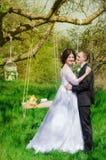 Le marié et la jeune mariée dans une robe blanche font du jardinage au printemps Photos stock