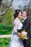 Le marié et la jeune mariée dans une robe blanche font du jardinage au printemps Images stock