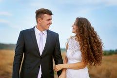 Le marié et la jeune mariée marchant sur le champ pendant le jour du mariage Photographie stock libre de droits