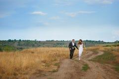 Le marié et la jeune mariée marchant sur le champ pendant le jour du mariage Photographie stock