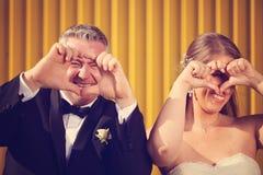 Le marié et la jeune mariée montrant l'AMOUR signent avec leurs mains Photo stock