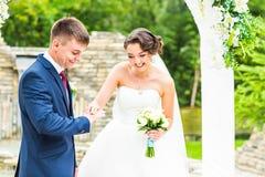 Le marié et la jeune mariée porte un anneau sur le doigt, cérémonie de mariage Or, symbole, religion, amour Images stock