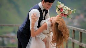 Le marié et la jeune mariée se sont fermés avec un bouquet pendant le baiser Georgia Kazbegi banque de vidéos