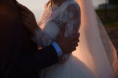 Le marié et la jeune mariée tiennent des mains au coucher du soleil, jour du mariage Concept de famille d'amour Images libres de droits