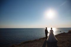 Le marié et la jeune mariée tiennent des mains au coucher du soleil, jour du mariage Concept de famille d'amour Image stock