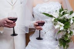 Le marié et la mariée avec des glaces de vin rouge Images stock
