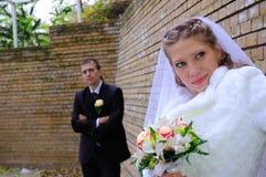 Le marié et la mariée près d'un mur photos stock