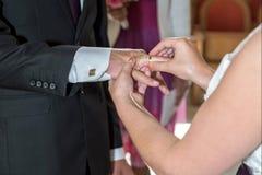 Le marié et les anneaux d'échange de jeune mariée Photo stock