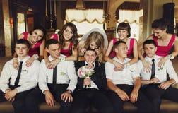 Le marié et les garçons d'honneur s'asseyent sur le sofa tandis que jeune mariée et demoiselles d'honneur Photo stock