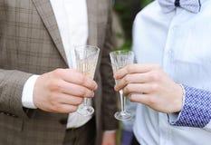 Le marié et son ami boivent du champagne des verres Image libre de droits