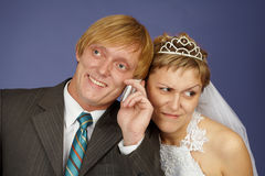 Le marié fait appel à un téléphone portable, mariée surprend Image stock