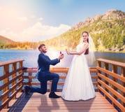 Le marié fait une proposition du mariage sur le pilier photo stock