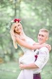 Le marié gai de jeunes ferme ses yeux tout en élevant la jeune mariée blonde Image libre de droits