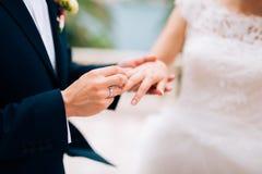Le marié habille un anneau sur le doigt de la jeune mariée à un mariage Image libre de droits