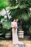 Le marié heureux étreint le dos de sourire de jeune mariée au fond des feuilles vertes énormes de la serre chaude Image libre de droits