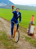 Le marié ivre sur un vélo tenant un bouquet de mariage court après une jeune mariée avec une bouteille à bière Photo libre de droits