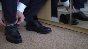 Le marié met dessus des chaussures banque de vidéos