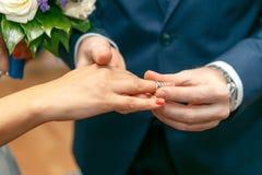 Le marié met dessus une bague de fiançailles sur le doigt de la jeune mariée Photo en gros plan Photos stock