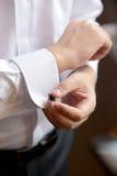 Le marié met sur le bouton de manchette Photos libres de droits