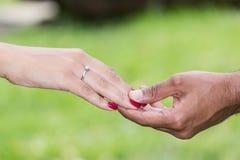 Le marié a mis la bague de fiançailles sur le doigt de la jeune mariée Photographie stock
