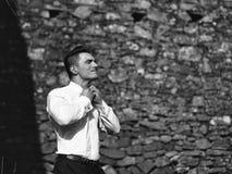 Le marié obtient habillé L'homme boutonne le collier de chemise Image stock