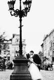 Le marié plie la jeune mariée au-dessus de la position derrière une vieille lanterne sur le CIT Images libres de droits