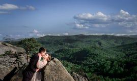 Le marié plie la jeune mariée au-dessus des pierres tout en embrassant photos libres de droits