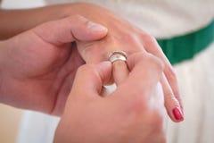 Le marié porte l'anneau sur le doigt de la jeune mariée Photographie stock libre de droits