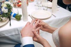 Le marié porte la jeune mariée d'anneau Cérémonie de mariage Anneau de l'or blanc et jaune Image libre de droits