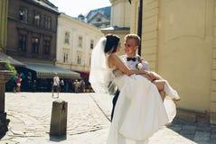 Le marié porte la jeune mariée dans des ses bras Image stock