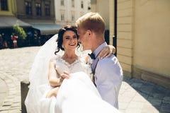 Le marié porte la jeune mariée dans des ses bras Photographie stock