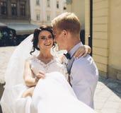 Le marié porte la jeune mariée dans des ses bras Photos stock