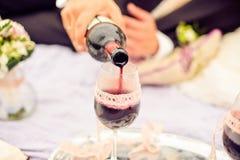 Le marié porte la jeune mariée par verre de vin photo stock