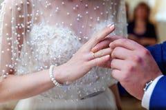 Le marié porte un anneau sur le ` s de jeune mariée photographie stock libre de droits