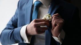 Le marié porte une cravate et un boutonniere de boutons de manchette