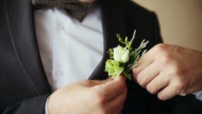 Le marié prend le boutonniere de mariage au costume clips vidéos