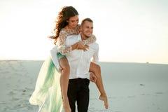 Le marié ramène la jeune mariée sur le sien à travers le sable dans le désert Fin vers le haut Photographie stock