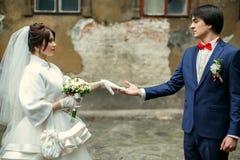 Le marié regarde avec amour une jeune mariée tenant son bras dans un glov blanc Photo stock
