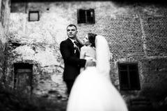 Le marié regarde en avant tout en étreignant une jeune mariée Photos stock