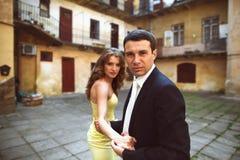 Le marié regarde sérieusement tout en tenant la main de la jeune mariée Photos libres de droits