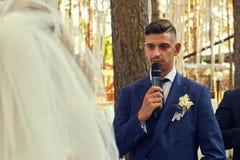 Le marié regarde une jeune mariée avec amour tout en disant son serment Image libre de droits
