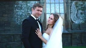 Le marié romantique beau et belle la jeune mariée blonde posant près du vieux mur se retranchent clips vidéos