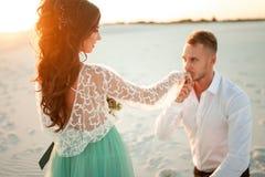 Le marié se tient avant jeune mariée sur un genou dans le désert sur le coucher du soleil et le ki Photo libre de droits
