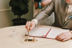 Le marié signe des documents dans le bureau d'enregistrement photographie stock