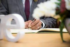 Le marié signe le certificat Photographie stock