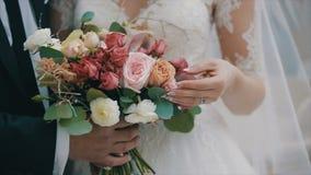 Le marié tient le beau bouquet l'épousant La jeune mariée touche des fleurs Bouquet nuptiale le jour du mariage banque de vidéos