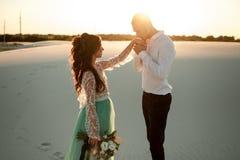 Le marié tient et embrasse la main du ` s de jeune mariée dans le désert au coucher du soleil fin Photos stock