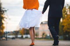 Le marié tient la jeune mariée pour une robe Vue arrière Concept de épouser accrochant en automne Photo libre de droits